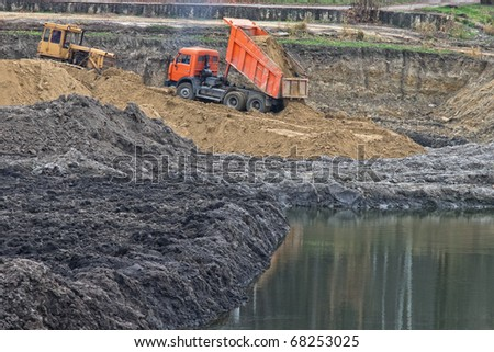 Dumper truck unloading sand onto construction site with water - stock photo