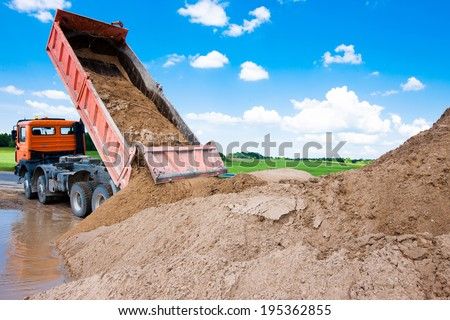 Dumper truck unloading soil or sand at construction site during road works at blue sky background - stock photo