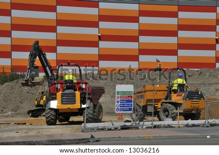 Dumper trucks and excavator machine at work construction site - stock photo