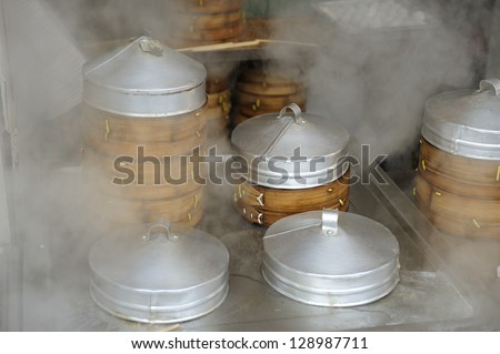 Dumplings cooking inside traditional bamboo steamers in outdoor restaurant in Shanghai - stock photo