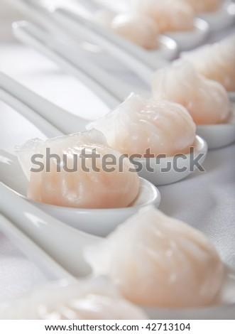 dumplings served on white spoons - stock photo