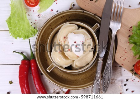 Dumplings with cheese in a ceramic dish on white wooden table