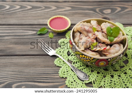 Dumplings with cherries on wooden background - stock photo