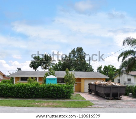 Dumpster and Port A Potty Suburban Ranch Style Home Landscaped with Shrubs - stock photo