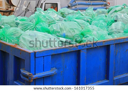 Dumpster container with green bags for recycling - stock photo