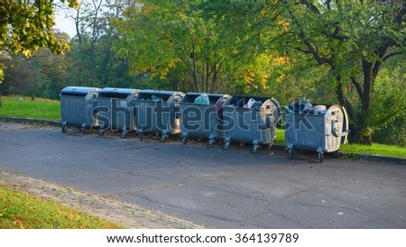 Dumpsters by the walking path in a park