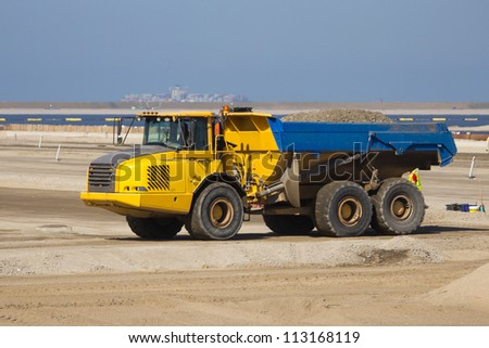 Dumptruck at a construction site in the harbor of Rotterdam. - stock photo