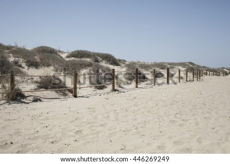 Dune beach with some vegetation and wood little fence in the south of Spain - stock photo
