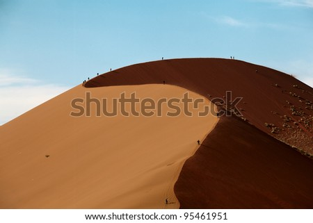 dune in the desert with people walking