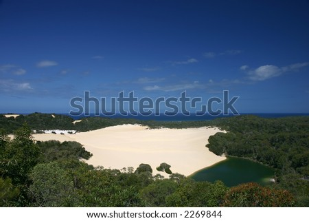 Dune in the middle of the rain forest, with a small green lake (Fraser Island, Australia) - stock photo
