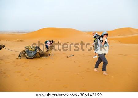 Dunes Erg Chebbi near Merzouga, Morocco - tourist during a camel tour into the erg - stock photo