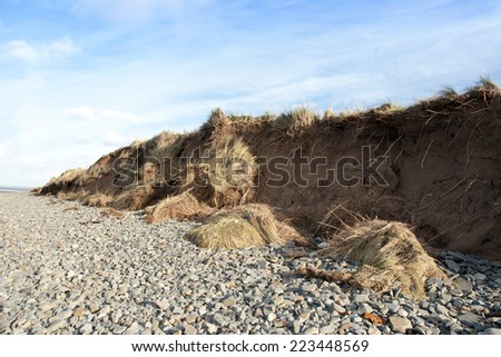dunes that have suffered extreme coastal erosion damage due to big storm waves - stock photo