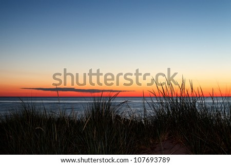 Dunes with grass silhouetted by a summer sunset over Lake Michigan. - stock photo