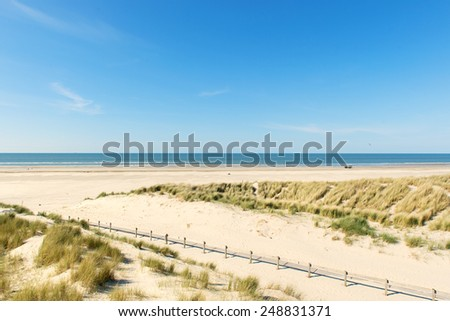 Dunes with path and fence at the coast - stock photo