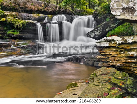 Dunloup Falls on Dunloup Creek is a beautiful West Virginia waterfall about two miles from the New River and the old abandoned railroad boom town of Thurmond. - stock photo
