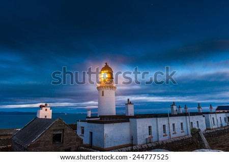 Dunnet Head Lighthouse, the most notherly point of the UK mainland at dusk with Scarpa Flow in background - stock photo
