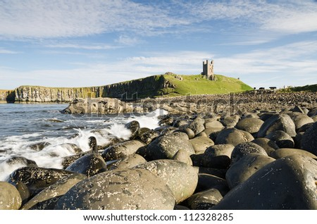 Dunstanburgh Castle from north / Iconic Dunstanburgh castle ruin built in the 14th century viewed from the northern rocky shoreline - stock photo