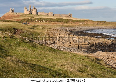 Dunstanburgh castle on Northumberland coast in North-East England - stock photo