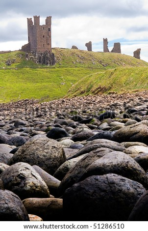 Dunstanburgh Castle seen from rocky beach - stock photo