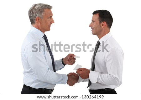 duo of businessmen exchanging visit cards - stock photo