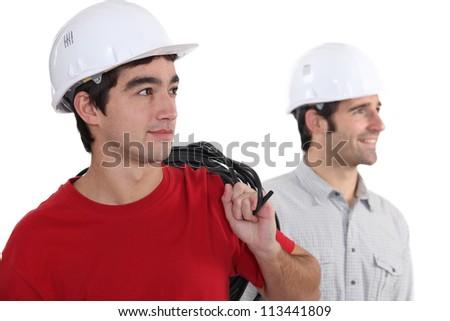 duo of electricians in studio - stock photo