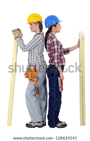 duo of female carpenters standing back to back in profile - stock photo