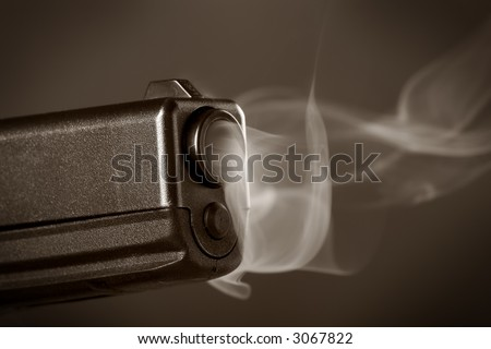 Duotone macro photo of a smoking semi-automatic pistol - stock photo