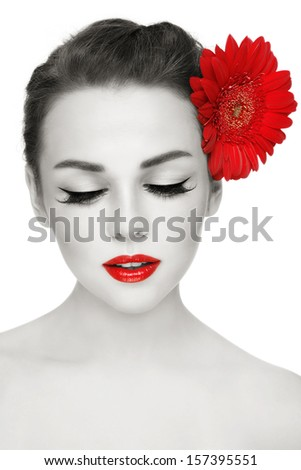 Duotone portrait of young beautiful woman with stylish make-up and red gerbera on white background - stock photo