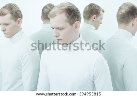 Duplicated image of sad, sick man suffering from bipolar disorder, standing in white interior - stock photo