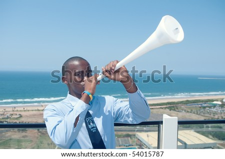 DURBAN - MAY 04: Vuvuzuela is the trumpet of south african soccer fans.  A southafrican student singing it at the durban new stadium, may 04 2010 in Durban, SouthAfrica - stock photo