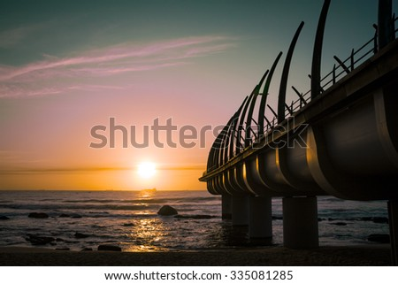Durban Pier in Umhlanga South Africa in the sunrise over horizon of indian ocean - stock photo