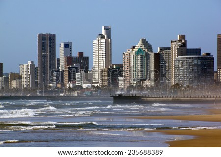 "DURBAN, SOUTH AFRICA - DECEMBER 4, 2014 : Early morning rough sea against city skyline on ""Golden Mile"" beach front in Durban, South Africa"