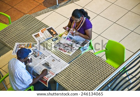 Durban, South Africa - March 10 2010: A couple reading the newspaper in  the Entrateinmet World and Casino, traditional meeting point of indian community