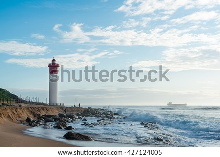 DURBAN, SOUTH AFRICA - MARCH 12, 2016: Umhlanga Rocks Lighthouse with fishermen and people walking on the promenade. Ship on the Indian Ocean in the background