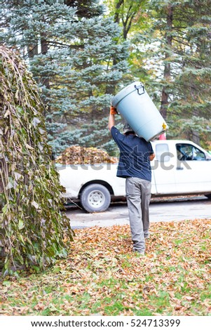 During fall clean up a man carries a trash can full of leaves to dump into the back of a waiting pickup truck