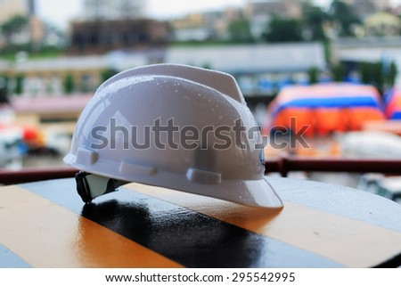 during the break works white hard hat and gloves lying on the ship's bitts - stock photo