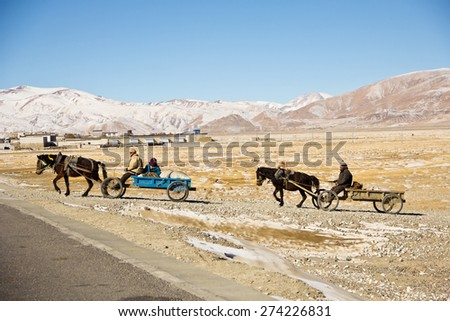 DURING THE ROAD FROM TIBET TO NEPAL - JANUARY 18: Tibetan nomad load Their stuffs on their horse carriages move toward the new palce on January 18, 2013 on the road from Tibet to Nepal. Tibet. - stock photo