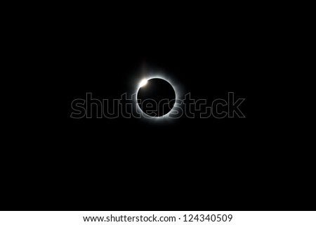 During the 2012 total solar eclipse the moon has completely covered the sun, leaving only a ring of light where the sun has been eclipsed.  A diamond ring appears as the moon slips off the sun. - stock photo
