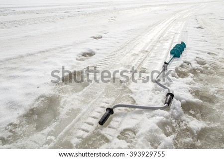 during the winter fishing on the ice borer lies near traces of the legs and snowmobile - stock photo