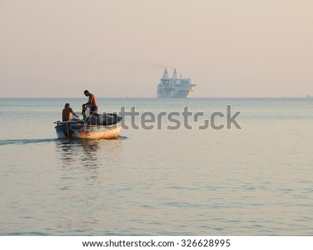 DURRES, ALBANIA - August 31, 2015: Fishermen in an old boat, big modern ship on the horizon. Albania has two faces - backwardness and poverty versus the new modern life.