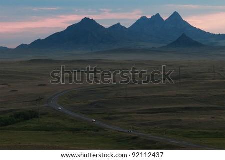 Dusk and road in desert mountains, Kazakhstan - stock photo