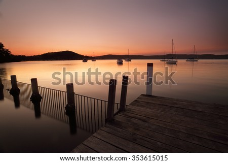 Dusk colours  fill the sky and reflect in the waterfront of Yattalunga on the Central Coast of Australia.  A perfect place to unwind, fish or swim.  Yattalunga in aborignal means Watering Place. - stock photo