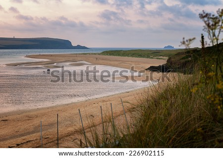 Dusk on the River Camel in Cornwall, UK.  It is low tide and people are walking their dogs on the beach.  This image has an intentional filtered look. - stock photo