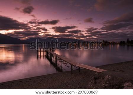 Dusk reflection at a jetty by Lake Te Anau, New Zealand - stock photo