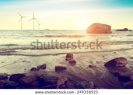 Dusk sea, near the reef and the distant wind turbines. - stock photo
