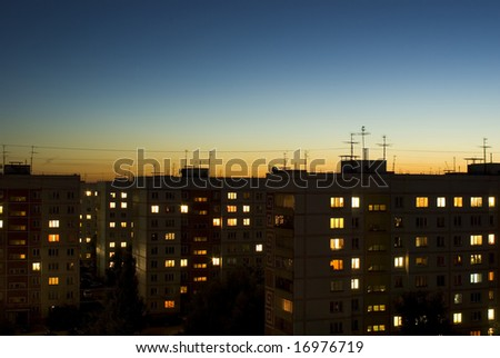 dusk sky and houses with lit windows background - stock photo