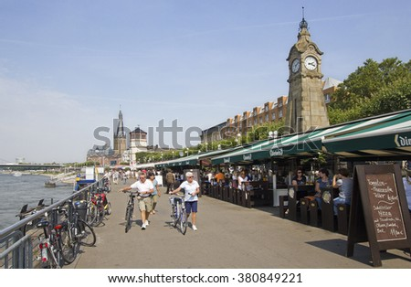 Dusseldorf, Germany - August 22, 2013: Elderly couple with bikes walk on the river promenade in Dusseldorf, Germany on  August 22, 2013. - stock photo