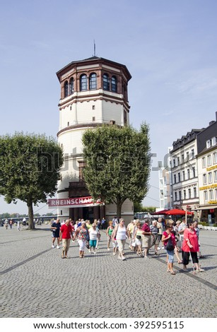Dusseldorf, Germany - August 22, 2013: Tourists walking on the Burgplatz and the tower of the Schiffahrt musem in Dusseldorf, Germany on  August 22, 2013.