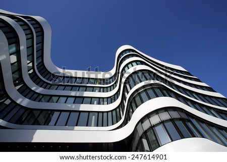 DUSSELDORF, GERMANY - FEBRUARY 2, 2014: A curved office building with white stripes and dark windows on February 2, 2014 in Dusseldorf. - stock photo