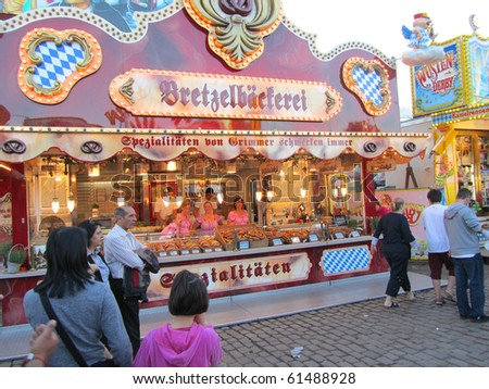 DUSSELDORF, GERMANY - JULY 24: Visitors at Pretzel Stall at Kirmes on July 24, 2010 in Dusseldorf, Germany. Kirmes is the biggest summer fair on the north Rhein in Germany. - stock photo